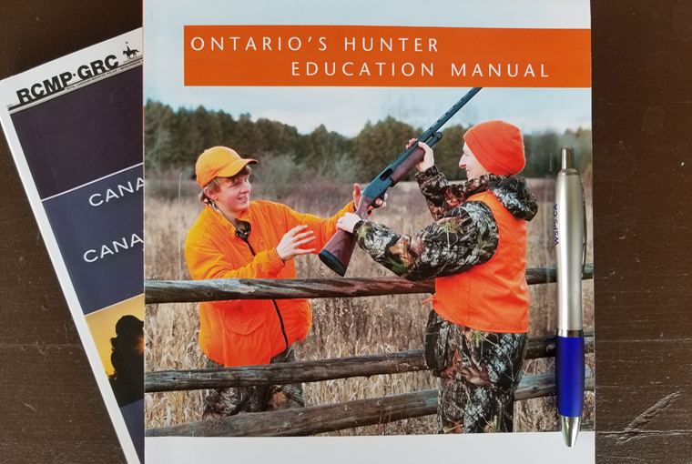 Ontario Hunter Education and Canadian Firearms Course manuals displayed on a desk.