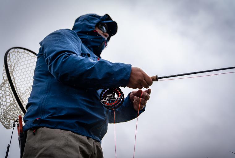Upward view of a man fly fishing
