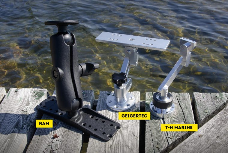 Three electronic mounting brackets displayed on a wooden dock