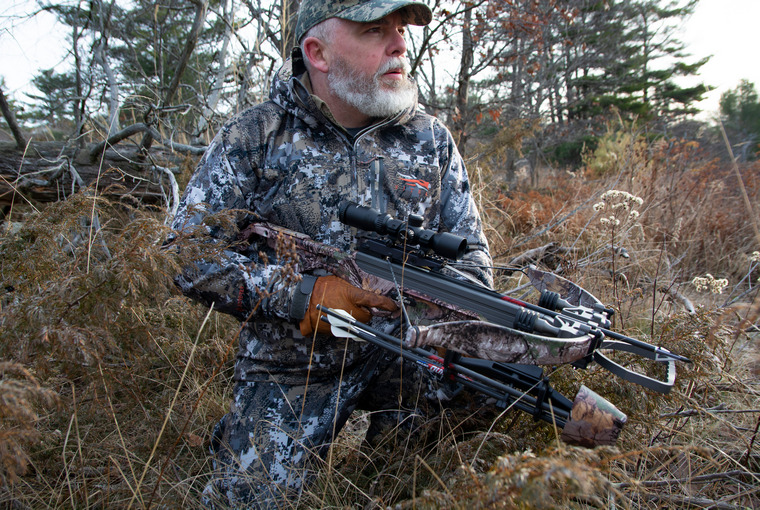 Bow hunter in the field waiting to see a deer