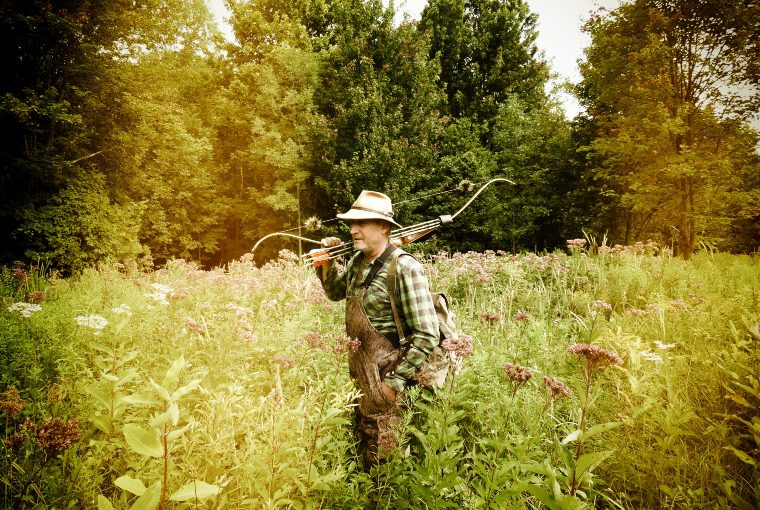 Male hunter wearing overalls and a plaid shirt carries traditional bow over shoulder as he walks through tall grass and wilderness.