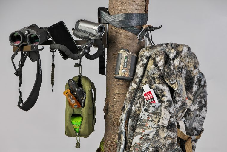 Binoculars, a black iphone, a video camera, a camouflage backpack, and other accessories hang tied on a tree.