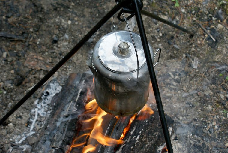 Close-up of a silver coffee pot hanging over a campfire.
