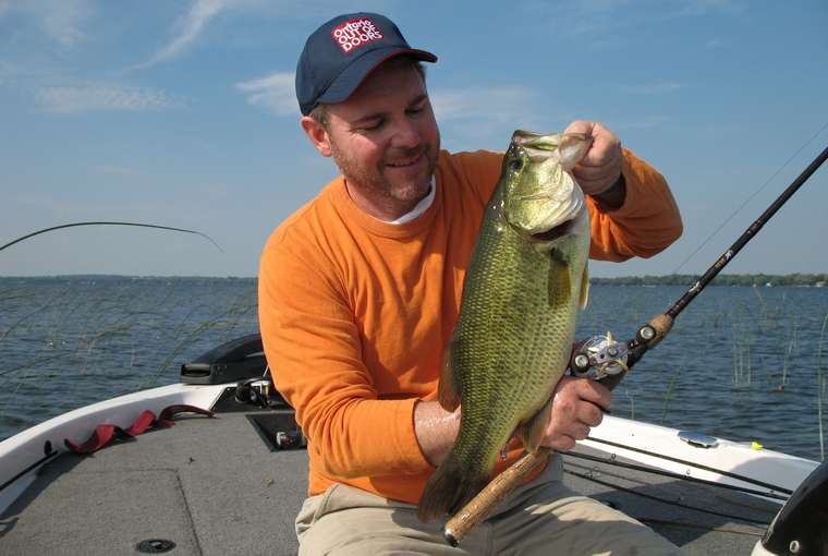 Proud angler presents a hefty largemouth bass while sitting on the deck of his boat positioned on a weed bed on the lake.
