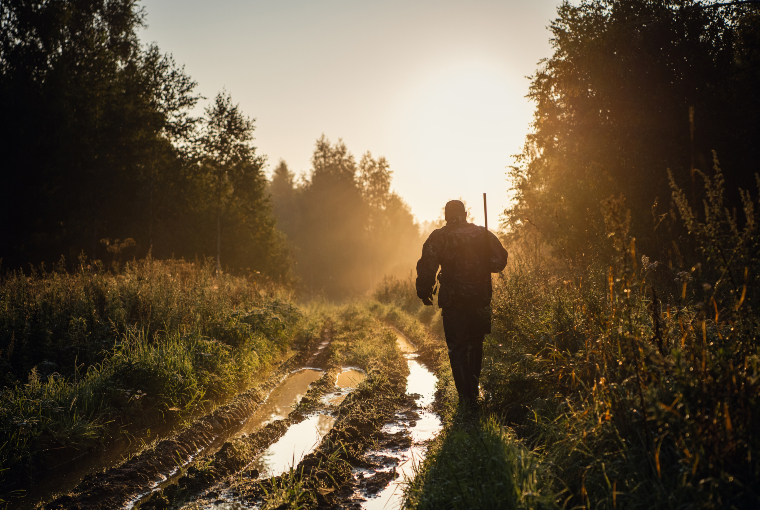 Hunter walks through muddy and grassy open trail towards sunlight.