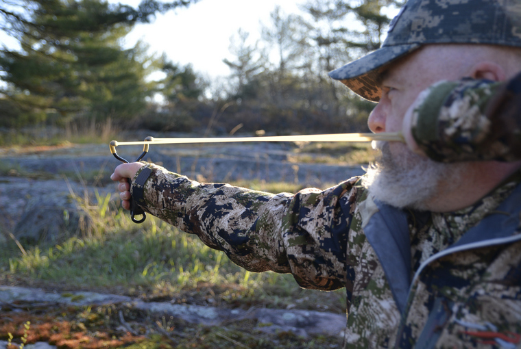 Bearded hunter wearing camouflage attire pulls back sling shot and takes aim into wooded area with sun shining.
