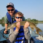 Eleven-year-old River Palhad of Delhi was delighted to pose for her mom, Kelly, after catching her first pike. She was using a yellow and red Hula Popper in the Waterford Ponds after getting a few pointers from her dad, Joe.