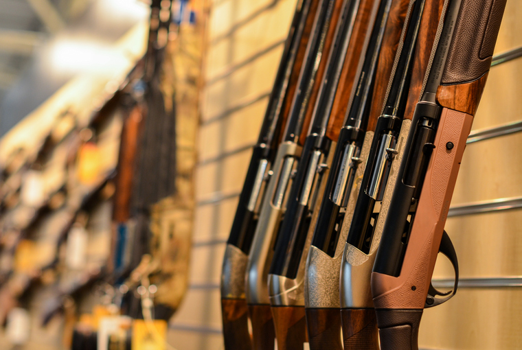 Series of semi-automatic shotguns leaning against a wall in a retail setting.