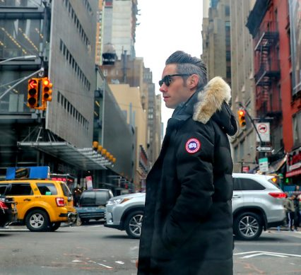 a man turns his head at a busy Toronto crosswalk, wearing a Canada Goose coat