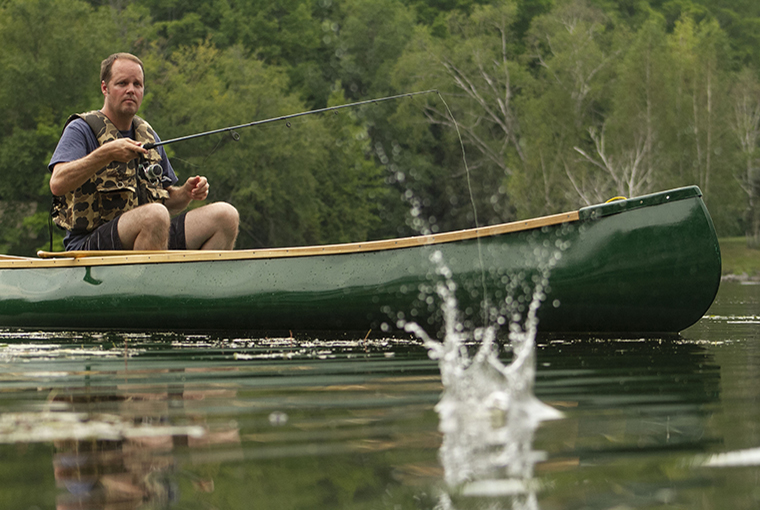 man casting lure from a canoe